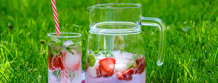 A glass and pitcher of refreshments on grass
