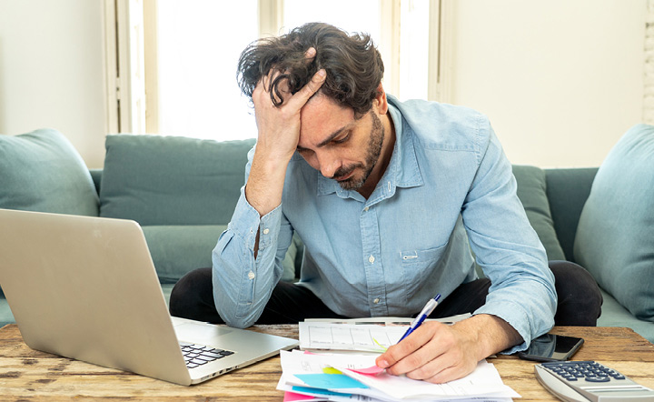 Man sitting on a couch, hand in hair, paying paper bills next to laptop