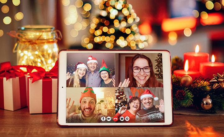 Four people gather on screen for virtual holiday party.