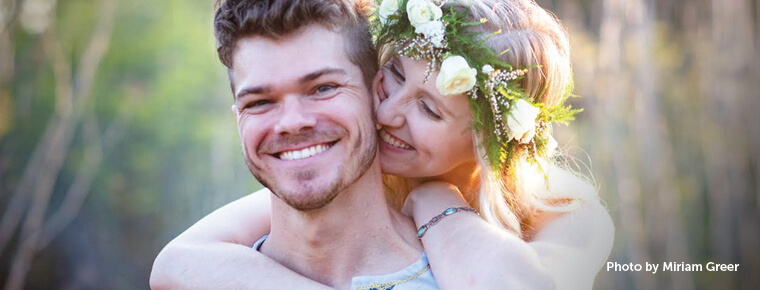 A man smiles at the camera while a woman wearing a flower wreath on her head hugs him from behind