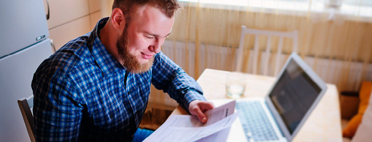 Bearded man sitting at a kitchen table, looking down at tax forms, a laptop open in front of him