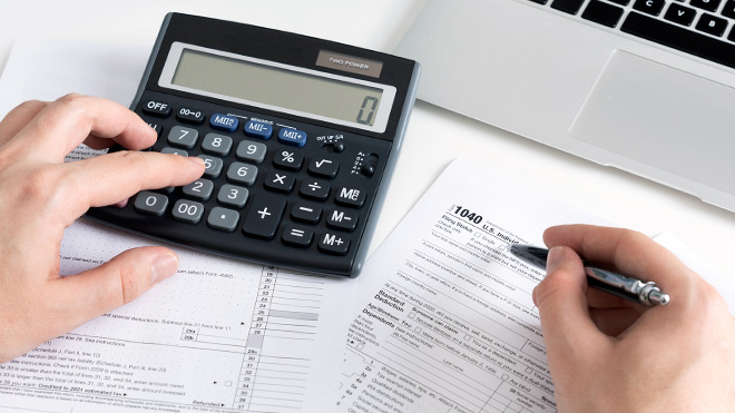 Image of tax documents and calculator in front of laptop