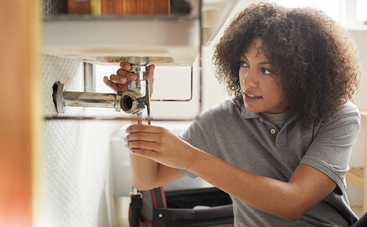 Consumer Checkbook Program - Woman fixing plumbing